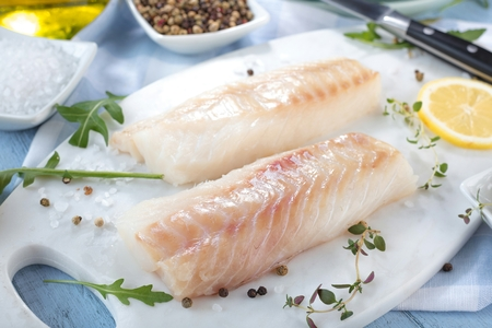 Fresh fish, raw cod fillets with addition of herbs and lemon Stockfoto