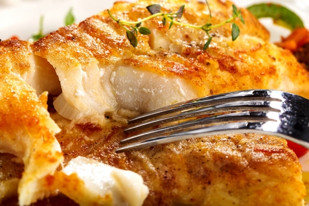 Fresh backed codfish filet on white table Imagens - 114434075