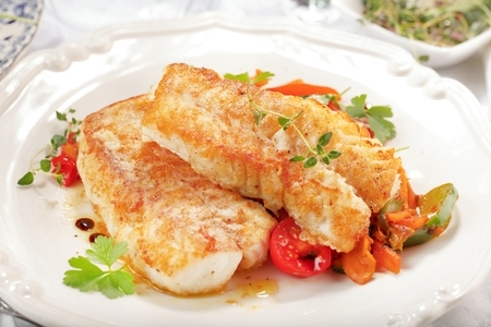Fresh backed codfish filet on white table