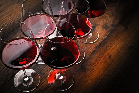 Copa de vino tinto sobre mesa de madera oscura.