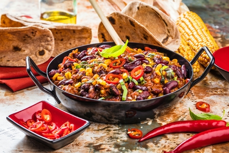 Chili con carne in a clay bowl on a concrete or stone rustic background- traditional dish of mexican cuisine.Top view