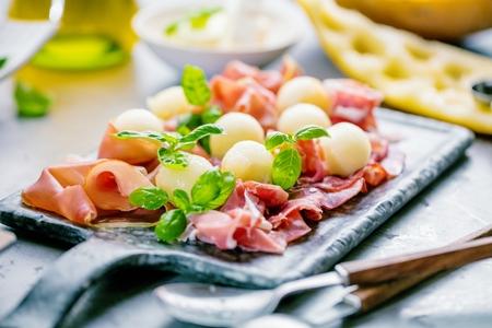Concepto de comida italiana con melón y jamón serrano, enfoque selectivo
