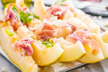 Concetto di cibo italiano con melone e prosciutto, messa a fuoco selettiva Archivio Fotografico