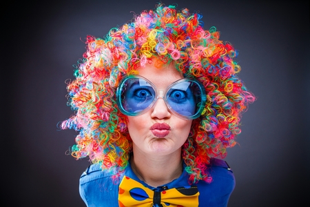 Portrait of beautiful party woman in wig and glasses Carnival