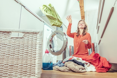 Young housewife is doing laundry with washing machine at home