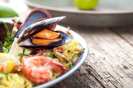Paella with seafood. Traditional spanish food closeup on wooden table