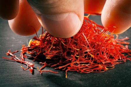 Heap of saffron threads on dark iron cast background