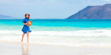 Happy traveller woman in blue dress enjoys her tropical beach vacation. Banco de Imagens