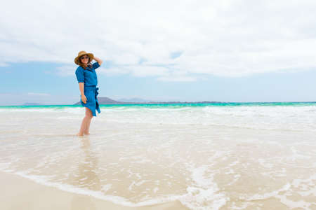 Happy traveler woman in blue dress enjoys her tropical beach vacation Banco de Imagens - 150819355