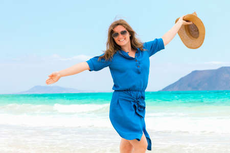 Happy traveler woman in blue dress enjoys her tropical beach vacation Banco de Imagens - 150819448