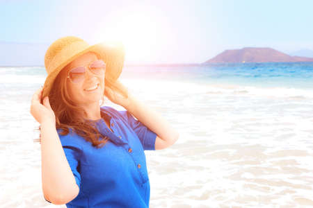 Happy traveler woman in blue dress enjoys her tropical beach vacation