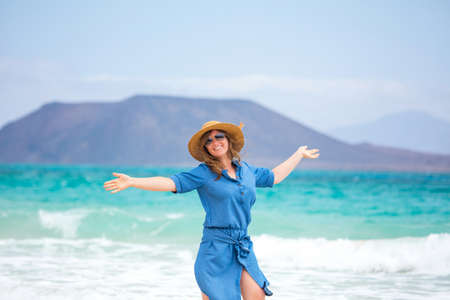 Happy traveler woman in blue dress enjoys her tropical beach vacation 스톡 콘텐츠 - 150819451