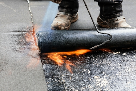 Flat roof installation. Heating and melting bitumen roofing felt. Stock Photo - 113464444