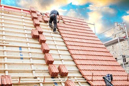 Dekarz pracujący na konstrukcji dachu budynku na budowie. Zdjęcie Seryjne