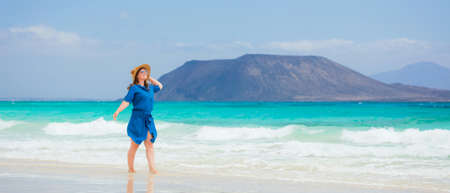 Happy traveler woman in blue dress enjoys her tropical beach vacation 스톡 콘텐츠 - 150819496