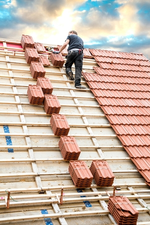 Roofer working on roof structure of building on construction site.