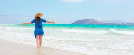 Happy traveler woman in blue dress enjoys her tropical beach vacation 스톡 콘텐츠 - 150819577