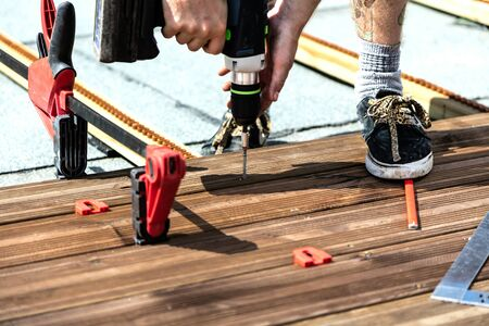 Handyman installing wooden flooring in patio, working with drilling machine.