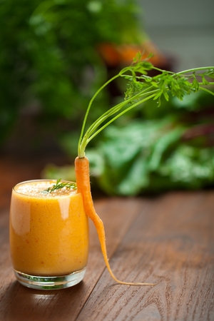 Carrot juice in glass and fresh carrots Healthy food on a grey stone background. 스톡 콘텐츠