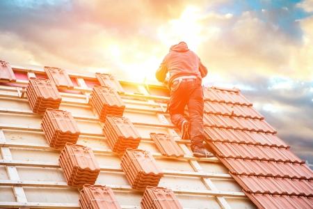 Dachdecker, der an der Dachkonstruktion des Gebäudes auf der Baustelle arbeitet.