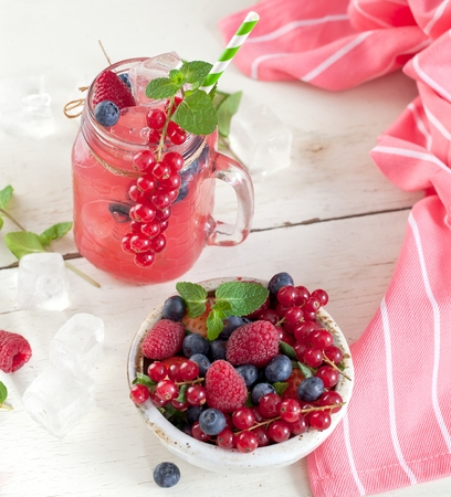 Summer Berry Drink. Lemonade with raspberry and blackberry with lemon, mint in mason jar on white table . Stock fotó