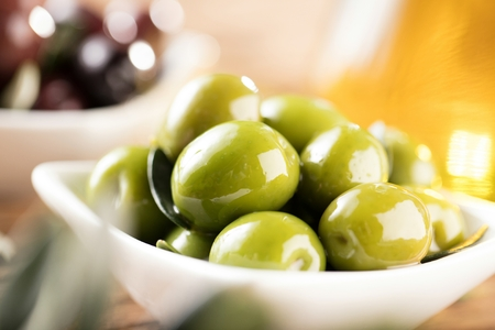 Olives and Olive Oil on wooden background in backlight.