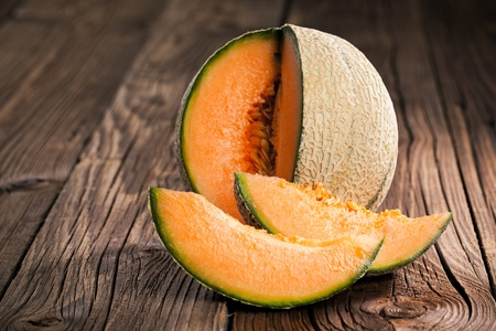 Melon with melon slices and leaves on a old wooden table. Organic food