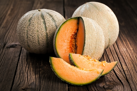 Melon with melon slices and leaves on a old wooden table. Organic food Stock Photo