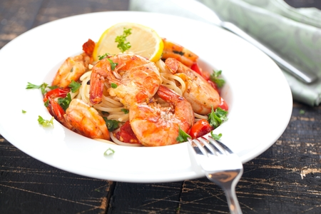 Stir-fried spaghetti with grilled shrimps and tomatoes - Italian fusion food style.