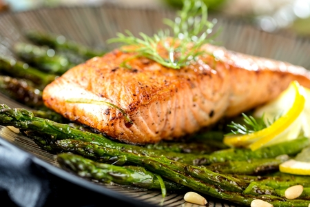 Grilled salmon and asparagus on wooden table close up.