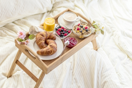 breakfast in bed with fruits and pastries on a tray