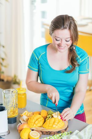 Fitness young woman drinking orange smoothie in Kitchen Reklamní fotografie - 145931426