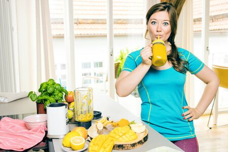 Fitness young woman drinking orange smoothie in Kitchen