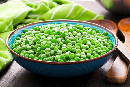 Heap of frozen pea on a old wooden table, top view.