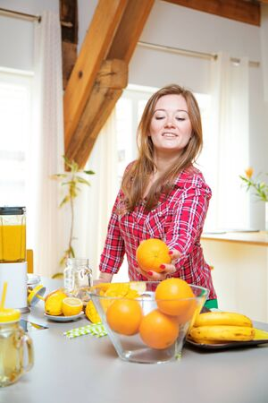 Young smiling woman making smoothie with fresh greens in the blender in kitchen at home.