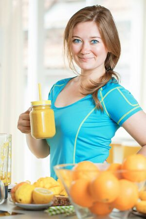 Fitness young woman drinking orange smoothie in Kitchen Reklamní fotografie - 145930719