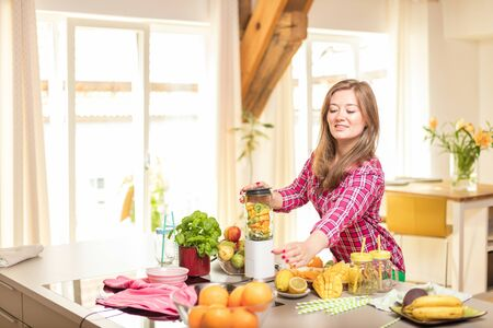 Young smiling woman making smoothie with fresh greens in the blender in kitchen at home. Reklamní fotografie - 145931128