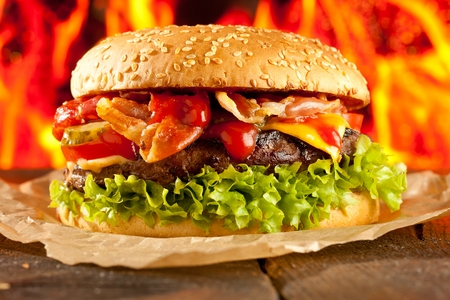 Close-up of home made burgers with fire flames. Stockfoto - 114527885