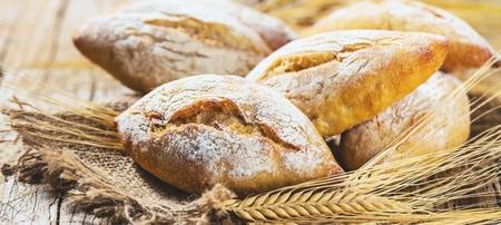 Différents types de pain frais sur table en bois. Assortiment isolé de pain sur fond marron.