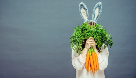 Funny woman with fresh carrot. Picture with space for your text. Stock Photo