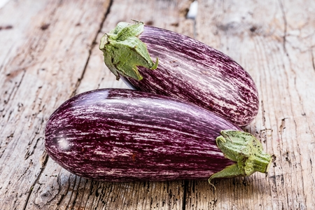Fresh purple eggplant graffiti on empty wooden background Foto de archivo