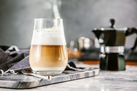 Glass cup of coffee latte on stone table
