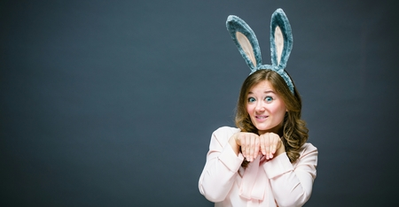 Festive bunny and eggs season. happy modern woman in Easter bunny ears isolated on grey background.