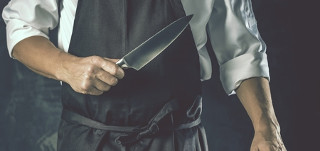 Chef cook holds a knife over dark grey background