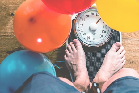 Bathroom scales with colorful balloons. Slimming concept.