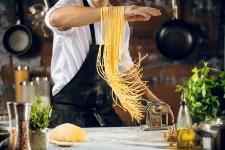 Chef-kok spaghetti noedels maken met pastamachine op keukentafel met wat ingrediënten rond. Stockfoto