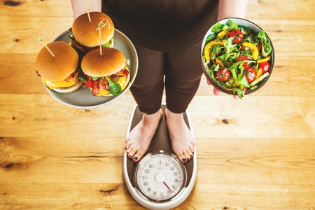 Healthy young woman looking at healthy and unhealthy plates of food, trying to make the right choice Banco de Imagens