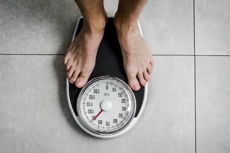 Balance de pesage en gros plan, hommes debout sur des balances Banque d'images
