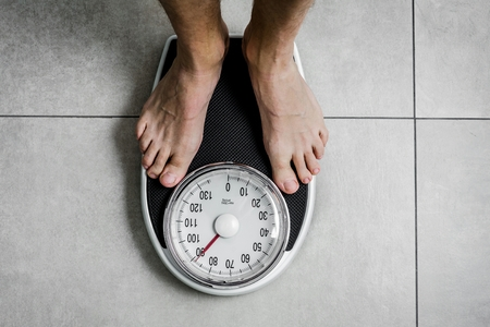 Close-up Weighing Scale ,Men standing on weigh scales Archivio Fotografico