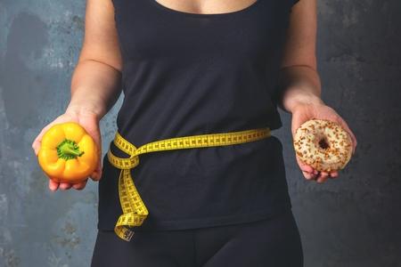 Gesunde junge Frau, die gesunde und ungesunde Teller mit Lebensmitteln betrachtet und versucht, die richtige Wahl zu treffen